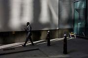 A black gentleman walks past an empty seat in a sunlit corner of a City of London lane.