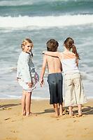 Three children standing at water edge on beach back view