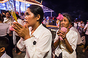 02 FEBRUARY 2013 - PHNOM PENH, CAMBODIA: Cambodian women pray for former King Norodom Sihanouk at a small shrine near the Royal Palace. Much of Phnom Penh has been shut down to honor former King Norodom Sihanouk, who ruled Cambodia from independence in 1953 until he was overthrown by a military coup in 1970. Only bars, restaurants and hotels that cater to foreign tourists are supposed to be open. The only music being played publicly is classical Khmer music. Sihanouk died in Beijing, China, in October 2012 and will be cremated during a state funeral royal ceremony on Monday, Feb. 4.    PHOTO BY JACK KURTZ