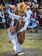 22 JULY 2016 - TENGANAN DUAH TUKAD, BALI, INDONESIA: A boy dances in the village temple after the pandanus fights in the Tenganan Duah Tukad village on Bali. The ritual Pandanus fights are dedicated to Hindu Lord Indra. Men engage in ritual combat with spiky pandanus leaves and rattan shields. They usually end up leaving bloody scratches on the combatants' backs. The young girls from the community wear their best outfits to watch the fights. The fights have been traced to traditional Balinese beliefs from the 14th century CE. The fights are annual events in the Balinese year, which is 210 days long, or about every seven months in the Gregorian calendar.    PHOTO BY JACK KURTZ