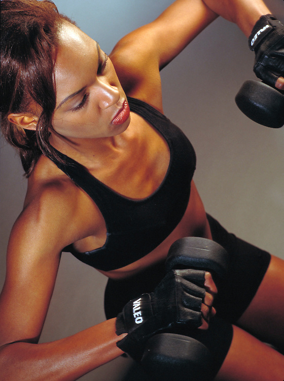 Young woman working out with dumbbells.