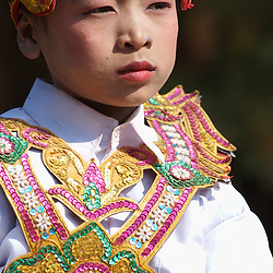 A young buddhist boy in traditional costume during a buddhist ceremony in Bagan, Myanmar.