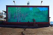 "Escape? Two workmen exit a door in a mural depicting a forest in Barentsburg, a Russian coal mining town in the Norwegian Archipelego of Svalbard. Once home to about 2000 miners and their families, less than 500 people now live here. There are no trees in Svalbard. This mage can be licensed via Millennium Images. Contact me for more details, or email mail@milim.com For prints, contact me, or click ""add to cart"" to some standard print options."