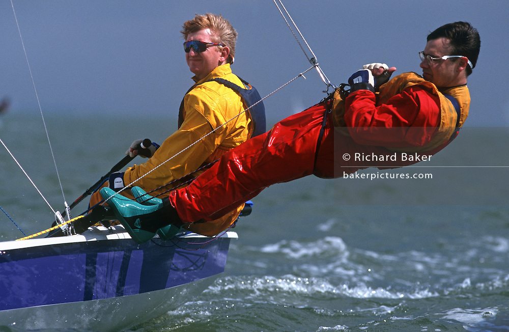 Weekend sailors crew a small laser racing yacht on windy seas of the Solent.