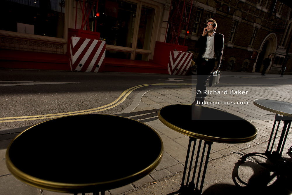 In strong sunlight, a businessman walks past cafe tables and construction site stripes.