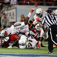 Miami Hurricanes defensive lineman Shayon Green (51) tackles Louisville Cardinals running back Dominique Brown (10)  during the NCAA Football Russell Athletic Bowl football game between the Louisville Cardinals and the Miami Hurricanes, at the Florida Citrus Bowl on Saturday, December 28, 2013 in Orlando, Florida. (AP Photo/Alex Menendez)