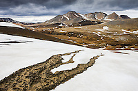 A small stream of mud runs over snow in the hills over Mount Kerlingarfjöll Hveradalir Valleys. Mount Fannborg and Snaekollur in background. Lítil aurskriða rennur yfir fönn ofan við efri Hveradali Kerlingarfjalla. Í baksýn eru fjöllin Fannborg og Snækollur.