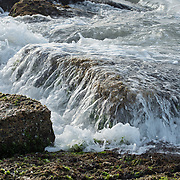 Wave in slow motion on top of rocks on jetty in Port Aransas, Texas.