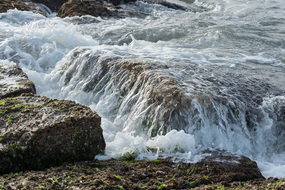 Wave in slow motion on top of rocks on jetty in Port Aransas, Texas.