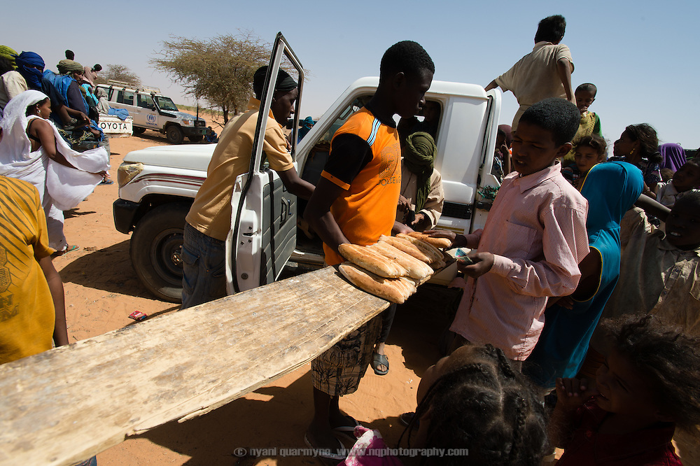 An enterprising bread seller from the Mbera refugee camp offers his wares to recently arrived refugees in the lead vehicles of a convoy as they wait for the rest of the convoy to catch up on the edge of the Mbera refugee camp in Mauritania on 6 March 2013.