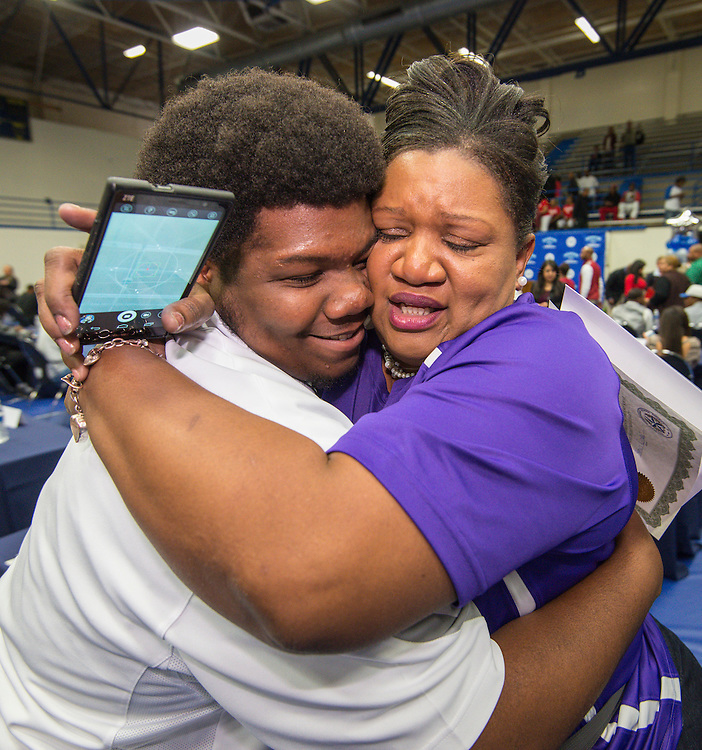 Scarborough's John Dunar, left, gets a hug during National Signing Day ceremonies for Houston ISD student athletes at the Pavilion at Forest Brook Middle School, February 3, 2016.
