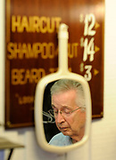Barber Tom Willette is reflected in a mirror hanging from the price sign in his barber shop, The Place. Willette has been cutting hair since 1954 in Burton Heights..Date Shot 6-19-2012.(Matt Gade | MLive.com)
