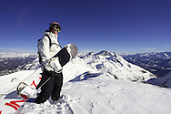 Female snowboarder stands on summit of mountain. Serre Chevalier, France