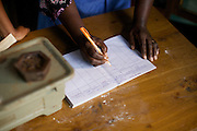 Joyce Marwa doing some record keeping. <br /> <br /> Joyce set up and now runs a bakery that bakes bread and cakes. She also processes nutritious flour (a mix of 5 grains)<br /> <br /> She attended MKUBWA enterprise training run by the Tanzania Gatsby Trust in partnership with The Cherie Blair Foundation for Women.