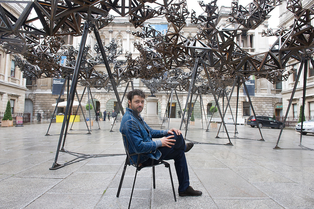 © London News Pictures. 29/05/15. London, UK. The artist Conrad Shawcross sits under his new installation 'The Dappled Light of the Sun' in the Royal Academy Courtyard, Central London. Photo credit: Laura Lean/LNP