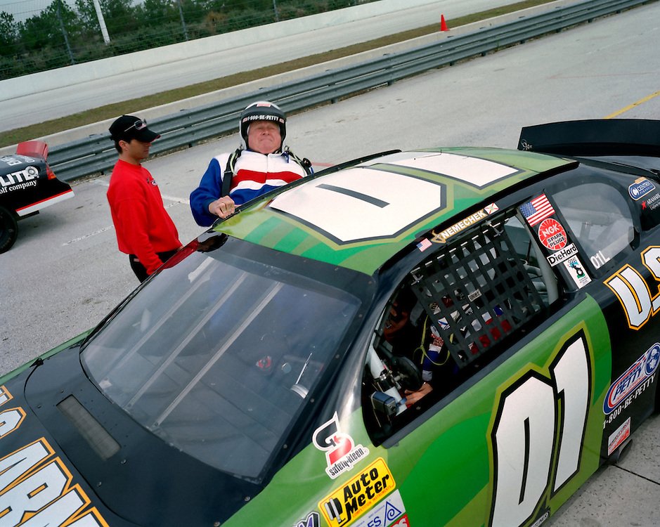 "NASCAR Ride-Along, Buena Vista, Florida, 2005.A man attempts to get in a NASCAR racing car at the Richard Petty Driving Experience.   ""If my husband got in that car, HE can,"" one observer remarked..Photo by Susana Raab."