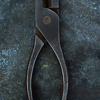 Vintage blunt-nosed pliers lying closed on tarnished metal sheet