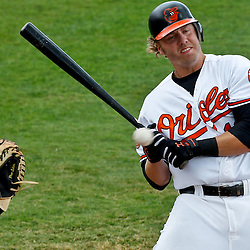 March 20, 2012; Sarasota, FL, USA; Baltimore Orioles third baseman Mark Reynolds (12) avoids being hit by an inside pitch during a spring training game against the Philadelphia Phillies at Ed Smith Stadium.  Mandatory Credit: Derick E. Hingle-US PRESSWIRE