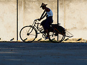 09 NOVEMBER 2014 - SITTWE, RAKHINE, MYANMAR:  A Burmese man rides his rickshaw bike taxi up Strand Road in Sittwe, Myanmar. Sittwe is a small town in the Myanmar state of Rakhine, on the Bay of Bengal. PHOTO BY JACK KURTZ