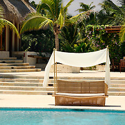 Cap Cana, Dominican Republic - April 12: A canopied bench sits next to the pool at the Caleton Beach Club in Cap Cana, Dominican Republic, April 12, 2007.