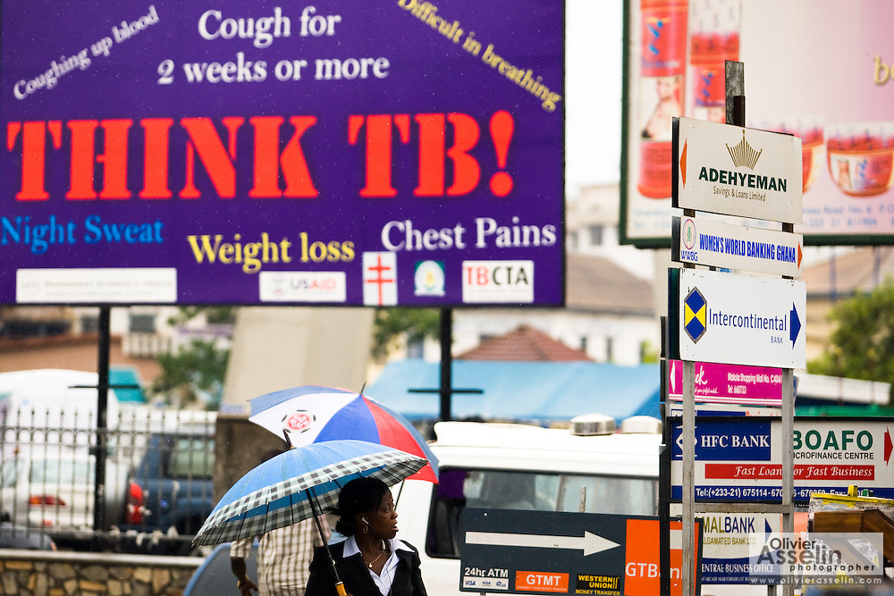 A woman stands under a sign promoting tuberculosis awareness in central Accra, Ghana on Tuesday June 16, 2009.