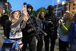 Concert-goers take selfies next to armed police as they depart following the One Love Manchester benefit concert for the victims of the Manchester Arena terror attack at Emirates Old Trafford, Greater Manchester.