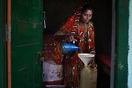 Savitri Devi poses for a portrait outside as she  pours kerosene at the self help shop for which she is the secretary, the shop distributes kerosene, sugar and salt in the village of Barmasia,  Jharkhand, India Wednesday, Oct. 10, 2012 (Photo/Elizabeth Dalziel for Christian Aid)