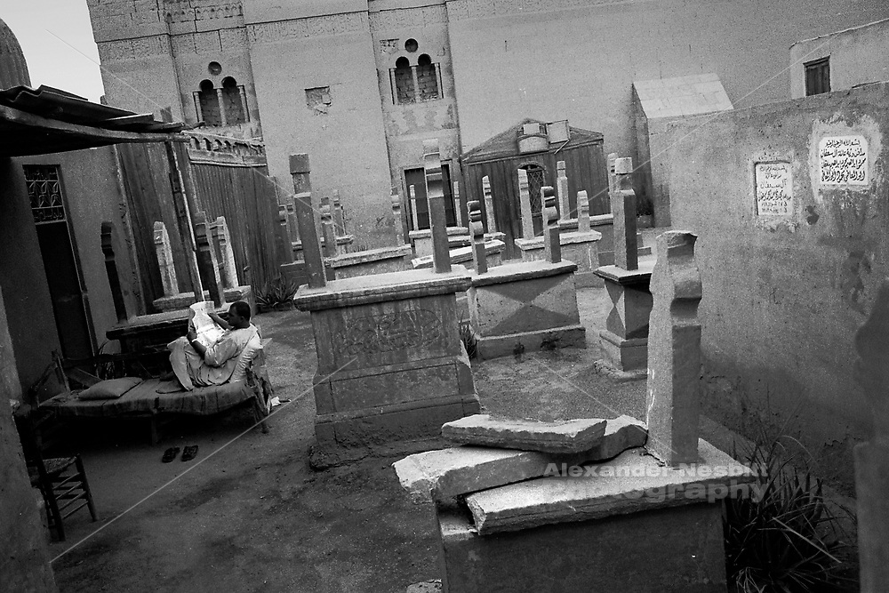 Cairo, Egypt, The City of the Dead, 1999 - A tomb guardian reads the paper.  For the inhabitants of the cemetery daily live goes on among the the graves.