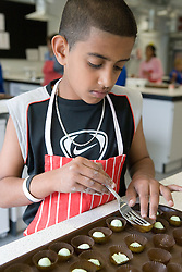 Asian boy making sweets in Food Studies lesson during his induction day,
