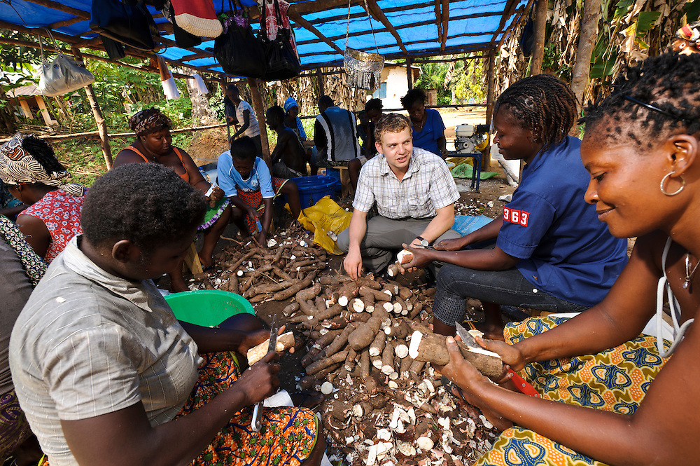 Rocco Falconer with men and women learning how to process cassava at a small factory run by Planting Promise, Newton, Freetown, Sierra Leone. Planting Promise is an organization dedicated to the development of education in Sierra Leone. Its aim is to bring opportunities to initiate self-run, self-supporting projects that offer real solutions to the difficulties facing the world's poorest country. They believe real and lasting development comes from below, from local projects that address specific needs, rather than large international models. To this end, they currently run five projects that aim to bring wealth into the country through business. The profits from these businesses are then used to support free education for children and adults...Through the combination of business with social progress, the charity hopes that they are providing real, lasting and profound changes for the better, by promoting sustainable and beneficial industry in the country, and putting it to the service to the needs of the people. As well as providing the income to fund the school, the farms will also be an example of successful commercial enterprise to teach the children in the school the viability of profit-making schemes that go beyond subsistence models, the only things the children of these desperately poor areas are accustomed to. By learning particular details of the challenges that they will face, the children will emerge from this school equipped to contribute in a real way to their society.