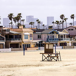 Photo of Newport Beach Skyline office buildings and waterfront luxury homes on Balboa Peninsula. Newport Beach is an upscale beach city in affluent Orange County in Southern California in the United States. Photo is high resolution and was taken in 2012.