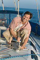 Man on Sailboat Tying Rope