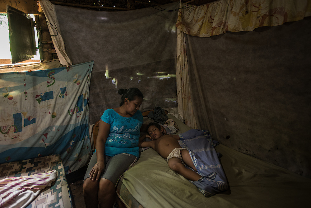 """EL DIQUE, VENEZUELA - MAY 24, 2016: Ana María Padrón comforts her son Aristides, 7, who is sick with malaria, at their home in El Dique. She said she felt helpless as  Aristides winced in pain, shaking from chills even though body as was burning up from a high fever.  Mrs. Padrón has been going to the malaria clinic regularly to try to find medicine for Aristides and her other son, Omar, who is also sick with Malaria, but has not been able to find it yet.  Doctors keep telling her to come back the next day.  """"We pray,"""" she said. 10 people in their family have contracted malaria, Mrs. Padrón's father died on May 3rd after contracting a fatal strain.  Their family lives next to a stagnant creek where malaria-carrying mosquitos thrive.  Their home does not have running water, so they keep several buckets around their home to catch rain water.  All the standing water attracts mosquitos. The townspeople in El Dique are gathering money to spray their own walls with pesticide to kill mosquitos for the first time. Doctors say they are only one of countless locations where government fumigators no longer arrive.  PHOTO: Meridith Kohut for The New York Times"""