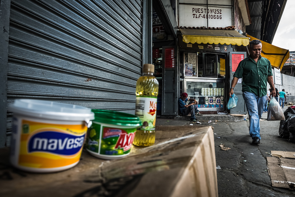 CARACAS, VENEZUELA - JANUARY 15, 2015: Blackmarket butter, soap and cooking oil  for sale at over five times the government regulated prices. When the police drove by, vendors rapidly hid all of their merchandise and ran into a back alley. Despite being a petro-state with one of the largest oil reserves in the world, basic food goods are difficult to find in stores across Venezuela.