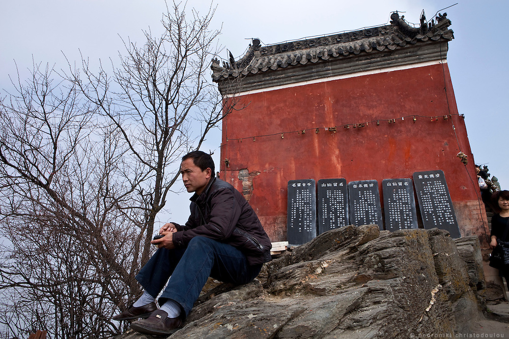 Asia, China, Hubei province.  Chinese man resting while enjoying the view at the Golden Palace on the Heavenly Pillar Peak of Wudang moutain (Wudang-san), a World Heritage mountain with many Taoist monasteries.