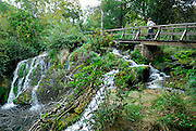 People walking on bridge and walkway over waterfall, Krka National Park, Croatia