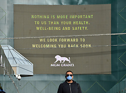 March 16, 2020, Las Vegas, Nevada, USA: A man with a mask walks by he MGM Grand hotel and casino as it flashes messages on their marquee that read 'Nothing is more important to us than your health, well-being and safety. We look forward to welcoming you back soon.' MGM Resorts International and Wynn Resorts will close their Las Vegas properties as of March 17 in light of the coronavirus pandemic. For most people, COVID-19 causes only mild or moderate symptoms, such as fever and cough. For some, especially older adults and people with existing health problems, it can cause more severe illness, including pneumonia. (Credit Image: © David Becker/ZUMA Wire)