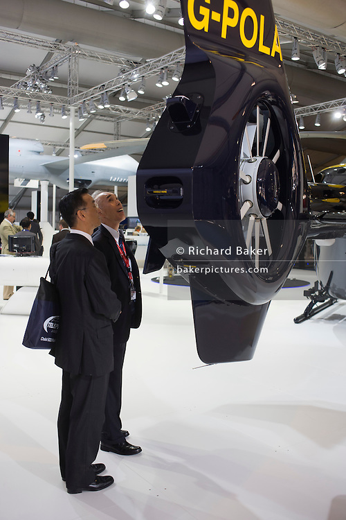 Two potential Asian buyers show interest at the tail rotos of an EADS-built police helicopter.