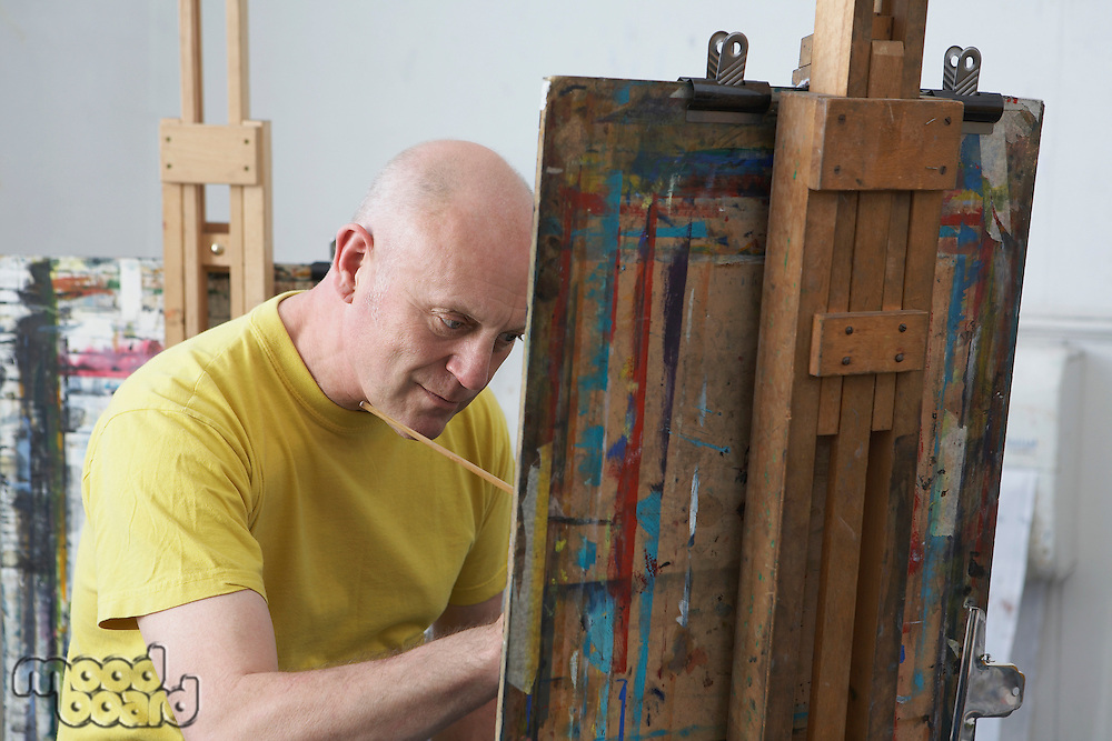 Mature male artist painting at easel