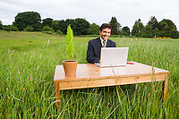 A late 30's early 40's mixed ethnicity (spanish french hispanic italian) businessman sitting at a desk in a field of high grass working on his laptop computer...Model Release: 20080602_MR_A
