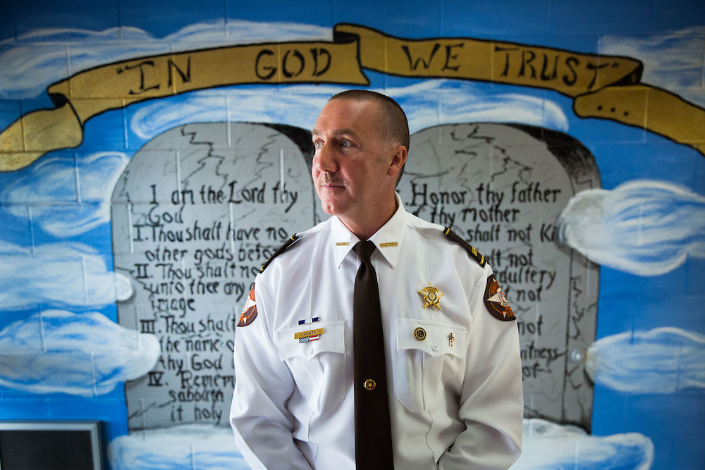 """Polk County Sheriff Johnny Moats poses for a portrait in front of a mural he had an inmate paint on the wall greeting everyone who walks inside the Polk County Public Safety Complex. Mr. Moats is among law officers who have affixed """"In God We Trust"""" decals to their cars. More than 50 departments across the country have done so in recent months. The mural includes the phrase """"In God We Trust"""" and the Ten Commandments. This portrait was taken on Oct. 1, 2015. Photo by Kevin D. Liles for The New York Times"""