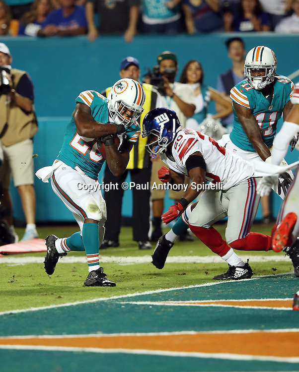 Miami Dolphins running back Lamar Miller (26) runs into New York Giants cornerback Prince Amukamara (20) as he runs for a first quarter touchdown good for a 7-3 Dolphins lead during the NFL week 14 regular season football game against the New York Giants on Monday, Dec. 14, 2015 in Miami Gardens, Fla. The Giants won the game 31-24. (©Paul Anthony Spinelli)