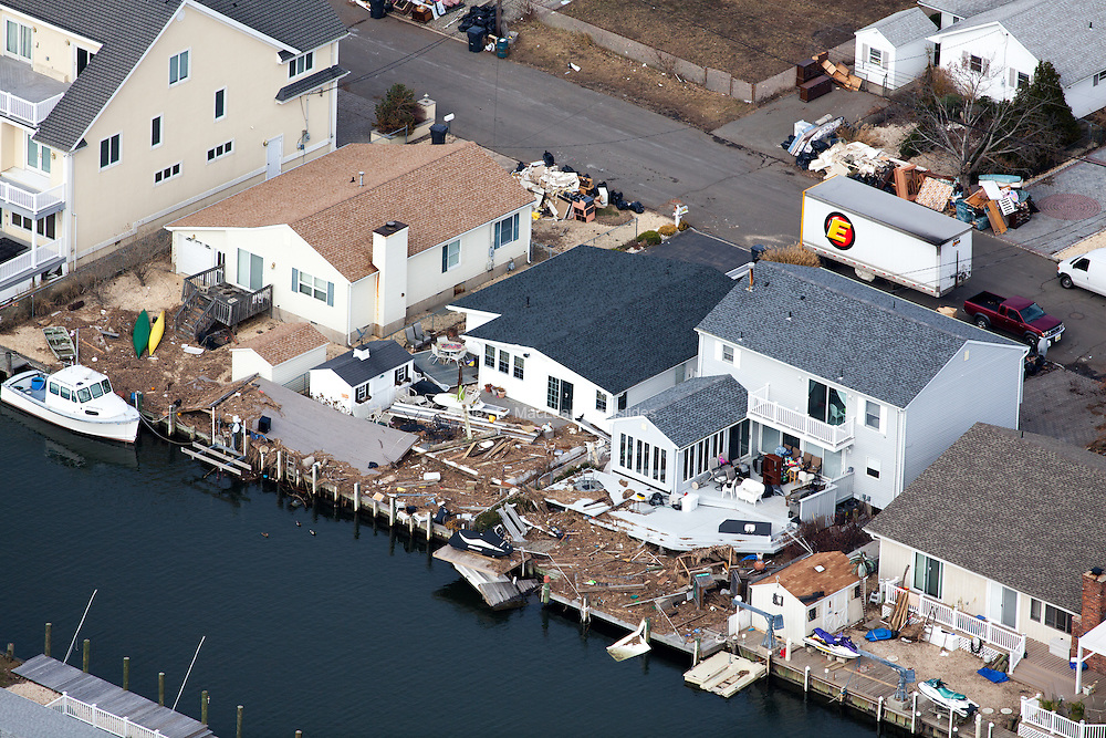 Debris and flood damage along lagoon key waterfront development. First floor furnishing at curb side waiting to be disposed of.