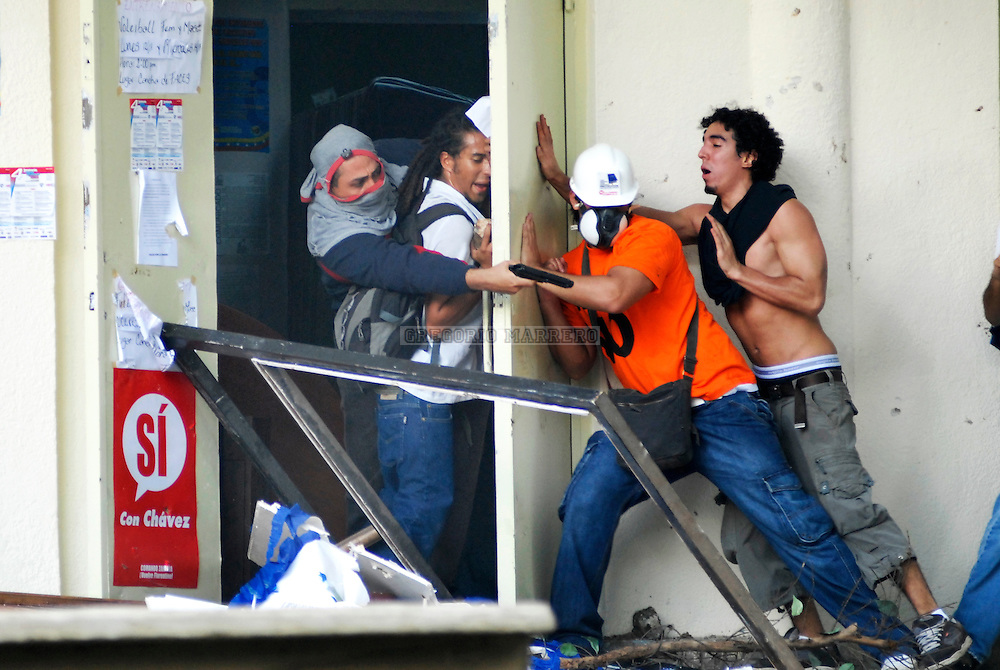 A gunman points his pistol against two students during clashes between students that support President Hugo Chavez and oppositions inside at the Venezuela's Central university in Caracas, Wednesday, Nov. 7, 2007. (Photo: Gregorio Marrero)