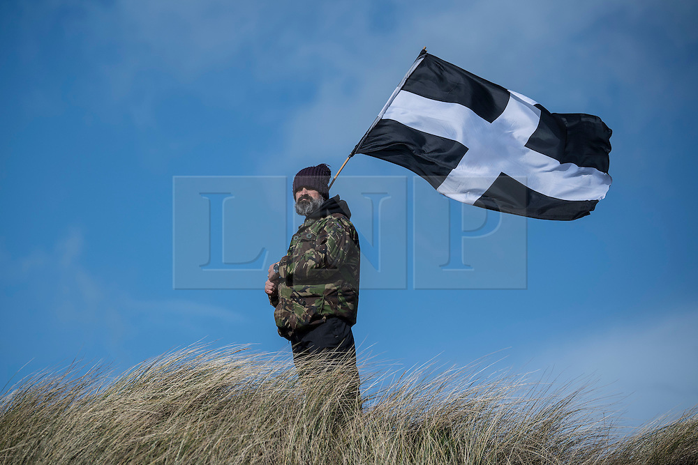 © Licensed to London News Pictures. 05/03/2017. PERRANPORTH, CORNWALL, UK. St Piran's flag blowing in the gale. St. Piran's Day in Cornwall. St Piran is the patron Saint of Sinners in Cornwall and it is his flag that is recognised as the Cornish flag. Today his arrival from Ireland to Cornwall is celebrated across Cornwall especially in Perranporth where it is believed that he landed. He set up an Oratory and a Church the remains of which have been recently uncovered in the sand dunes at Perranporth..  Photo credit: MARK HEMSWORTH/LNP