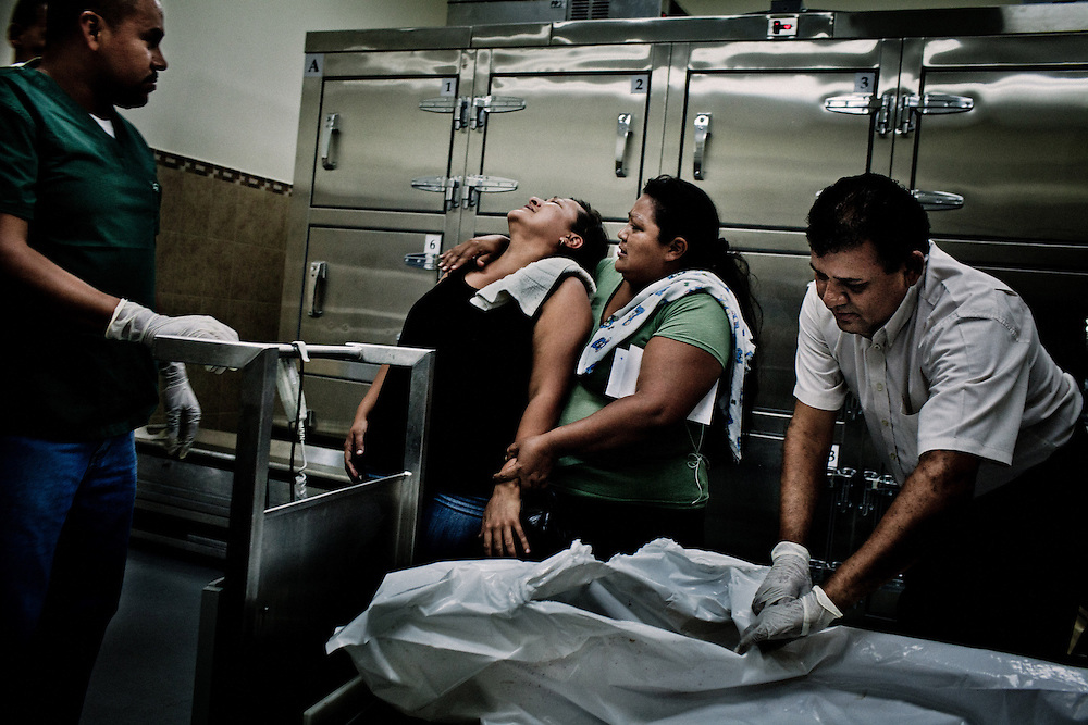 "Wendy Maritza Rodriguez, 38, (left) reacts after she recognized the body of her adopted son with her sister Estela Marisol Rodriguez, 37, (R) at the morgue of the Insituto Medico Legal of San Salvador, El Salvador. August 15, 2012.  Jonathan manuel Peña, 27, a former member of the gang Mara Salvatrucha was shot from the back the night before. He left the mara 6 years ago and had some of his tatoos erased, but for the ""mareros"" is difficult to leave their past, the gangs have a saying ""o vivis por la mara o moris por la mara"" ""either you live for the mara or you die for the mara"" meaning that there is no way out.  Photo/Tomas Munita"