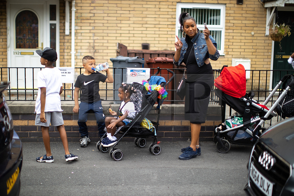 © Licensed to London News Pictures . 11/08/2018. Manchester , UK . People stop on Quinney Crescent and watch the procession as is passes through Moss Side . The annual Moss Side Caribbean Carnival procession , celebrating dance , music and Afro-Caribbean culture , which passes in a loop from Alexandra Park and through the streets of Moss Side . Photo credit : Joel Goodman/LNP