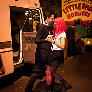 Couple dancing in street at the annual Greenwich Village Halloween parade, man dressed as priest and woman with red wig and tattoos on legs, New York, NY