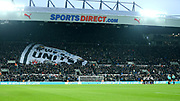 Newcastle United fans unveil a large banner in support of the team as the players gather in a huddle on the pitch during the Premier League match between Newcastle United and Swansea City at St. James's Park, Newcastle, England on 13 January 2018. Photo by Craig Doyle.