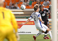 United defender Rodney Wallace heads the ball past Kansas City defender Michael Harrington. United defeated the Wizards 2-1 to earn their first points of the season.
